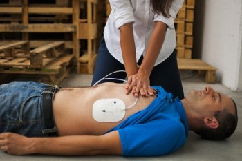 Woman practicing CPR on prone man wearing AED patches